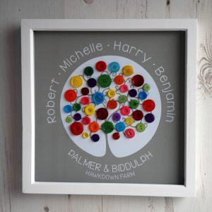 A medium family tree with rainbow buttons and the name of the family home on a light brown background